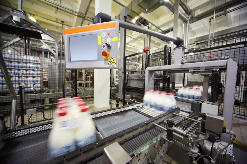 Conveyor with wrapped milk bottles at big factory; display of control computer