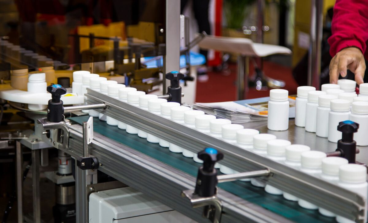 White plastic bottle on capsule filling machine conveyor belt in production line. Pharmaceutical industry